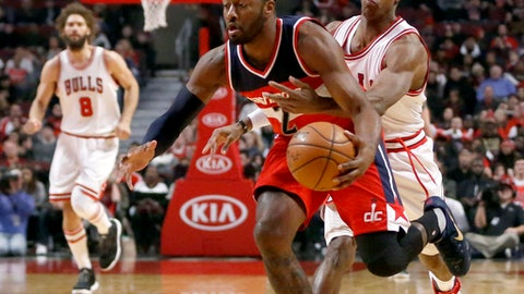 Washington Wizards' John Wall (2) drives to the basket as Chicago Bulls' Rajon Rondo tries to strip the ball from behind during the first half of an NBA basketball game Wednesday, Dec. 21, 2016, in Chicago. (AP Photo/Charles Rex Arbogast)