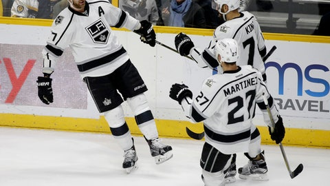 Los Angeles Kings center Jeff Carter (77) celebrates with Alec Martinez (27) and Dwight King (74) after Carter scored a goal against the Nashville Predators during the third period of an NHL hockey game Thursday, Dec. 22, 2016, in Nashville, Tenn. (AP Photo/Mark Humphrey)