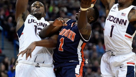 Auburn's Jared Harper (1) drives past Connecticut's Steven Enoch (13) and Christian Vital during the first half of an NCAA college basketball game in Hartford, Conn., on Friday, Dec. 23, 2016. (AP Photo/Fred Beckham)