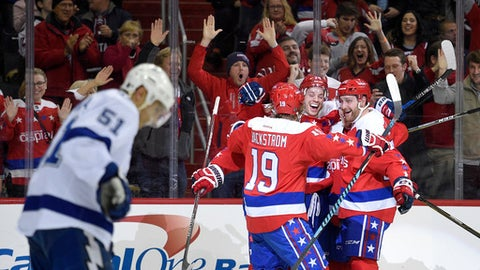 Washington Capitals defenseman John Carlson, second from right, celebrates his goal with center Nicklas Backstrom, of Sweden, (19) and Karl Alzner, right, during the first period of an NHL hockey game  as Tampa Bay Lightning center Valtteri Filppula (51), of FInland, skates by, Friday, Dec. 23, 2016, in Washington. (AP Photo/Nick Wass)