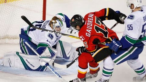 Vancouver Canucks' Alex Biega, right, takes a holding penalty on a Calgary Flames' Johnny Gaudreau, center, breakaway on Canucks goalie Jacob Markstrom, of Sweden, during the third period of an NHL hockey game in Calgary, Alberta, Friday, Dec. 23, 2016. (Larry MacDougal/The Canadian Press via AP)