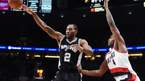 San Antonio Spurs forward Kawhi Leonard passes the ball as Portland Trail Blazers forward Maurice Harkless defends during the first half of an NBA basketball game in Portland, Ore., Friday, Dec. 23, 2016. AP Photo/Steve Dykes)