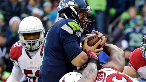 Seattle Seahawks quarterback Russell Wilson, center, is held back by Arizona Cardinals defensive end Calais Campbell (93) while retaining the ball on a touchdown-attempt in the first half of an NFL football game, Saturday, Dec. 24, 2016, in Seattle. (AP Photo/Ted S. Warren)