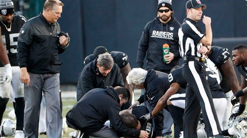 Oakland Raiders head coach Jack Del Rio, left, watches as quarterback Derek Carr, bottom, is tended to by trainers during the second half of an NFL football game against the Indianapolis Colts in Oakland, Calif., Saturday, Dec. 24, 2016. (AP Photo/Tony Avelar)
