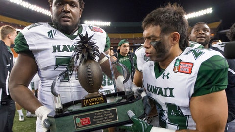 Hawaii offensive lineman RJ Hollis, left, and wide receiver Samson Anguay hold the Hawaii Bowl trophy after Hawaii defeated Middle Tennessee 52-35 in the NCAA college football game, Saturday, Dec. 24, 2016, in Honolulu. (AP Photo/Eugene Tanner)