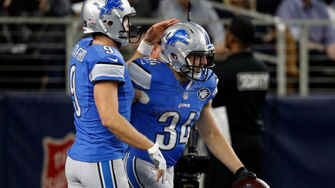 Detroit Lions' Matthew Stafford (9) celebrates with Zach Zenner (34) after Zenner scored a touchdown on a run in the first half of an NFL football game against the Dallas Cowboys on Monday, Dec. 26, 2016, in Arlington, Texas. (AP Photo/Brandon Wade)