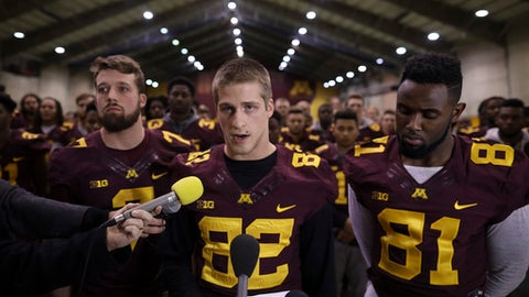 FILE - In this Dec. 15, 2016, file photo, University of Minnesota wide receiver Drew Wolitarsky, flanked by quarterback Mitch Leidner, left, and tight end Duke Anyanwu stands in front of other team members as he reads a statement on behalf of the players in the Nagurski Football Complex in Minneapolis, Minn. Interviews by The Associated Press revealed a lingering divide between an administration trying to actively investigate allegations from a woman who says she was pressured into sex with multiple football players and a team that was concerned about the fairness of the process. (Jeff Wheeler/Star Tribune via AP, File)