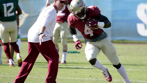 Florida State running back Dalvin Cook (4) runs as head coach Jimbo Fisher, left, looks on during NCAA college football practice, Tuesday, Dec. 27, 2016, in Fort Lauderdale, Fla. Florida State plays Michigan in the Orange Bowl Friday. (AP Photo/Lynne Sladky)