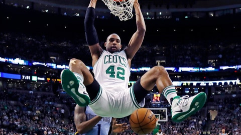 Boston Celtics center Al Horford (42) hangs from the rim after a dunk against Memphis Grizzlies forward Jarell Martin (1) during the first quarter of an NBA basketball game in Boston, Tuesday, Dec. 27, 2016. (AP Photo/Charles Krupa)