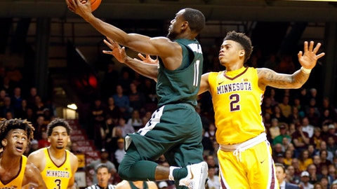 Michigan State's Lourawls Nairn Jr., center, lays up in from of Minnesota's Nate Mason, right, during the first half of an NCAA college basketball game, Tuesday, Dec. 27, 2016, in Minneapolis. (AP Photo/Jim Mone)