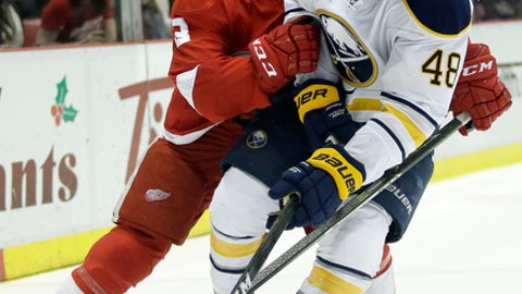Buffalo Sabres left wing William Carrier (48) is knocked off the puck by Detroit Red Wings defenseman Nick Jensen (3) during the first period of an NHL hockey game, Tuesday, Dec. 27, 2016, in Detroit. (AP Photo/Duane Burleson)