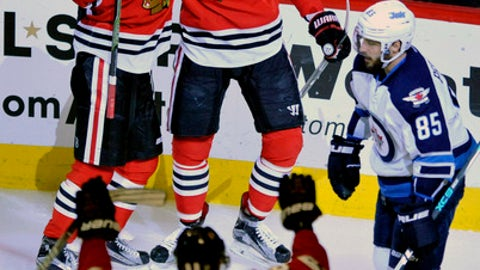 Chicago Blackhawks' Artem Anisimov (15) of Russia, celebrates with teammates Artemi Panarin (72) of Russia, and Patrick Kane (88) after scoring a goal while Winnipeg Jets' Mathieu Perreault (85) looks on during the second period of an NHL hockey game Tuesday, Dec. 27, 2016, in Chicago. (AP Photo/Paul Beaty)