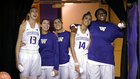 Washington starters Katie Collier (13), Natalie Romeo, Kelsey Plum, Heather Corral (14) and Chantel Osahor pull a curtain aside as they look into the arena before player introductions at an NCAA college basketball game against Washington State to start Pac-12 conference play, Tuesday, Dec. 27, 2016, in Seattle. (AP Photo/Elaine Thompson)