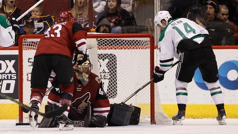 Dallas Stars' Jamie Benn (14) slips the puck past the pad of Arizona Coyotes goalie Mike Smith (41) for a goal as Coyotes defenseman Alex Goligoski (33) skates in during the second period of an NHL hockey game, Tuesday, Dec. 27, 2016, in Glendale, Ariz. (AP Photo/Ralph Freso)