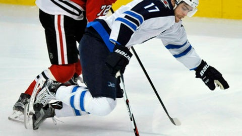 Winnipeg Jets' Adam Lowry (17) battles Chicago Blackhawks' Artemi Panarin (72) of Russia, for a loose puck during the first period of an NHL hockey game Tuesday, Dec. 27, 2016, in Chicago. Winnipeg won 3-1. (AP Photo/Paul Beaty)