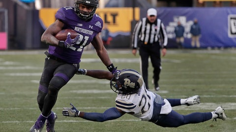 Northwestern running back Justin Jackson (21) runs the ball for a touchdown as he avoids a tackle by Pittsburgh defensive back Dennis Briggs (20) during the second quarter of the Pinstripe Bowl NCAA college football game, Wednesday, Dec. 28, 2016, in New York. (AP Photo/Julie Jacobson)