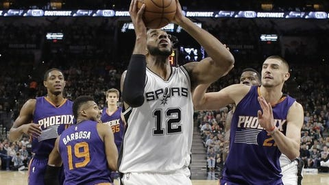 San Antonio Spurs forward LaMarcus Aldridge (12) shoots past Phoenix Suns center Alex Len (21) during the first half of an NBA basketball game, Wednesday, Dec. 28, 2016, in San Antonio. San Antonio Spurs won 119-98. (AP Photo/Eric Gay)