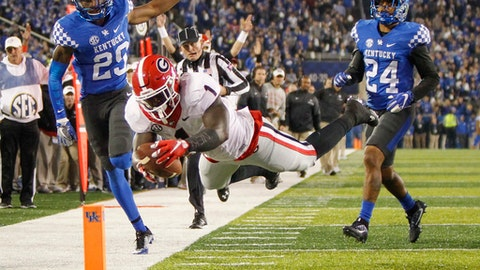 FILE - In this Nov. 5, 2016 file photo, Georgia running back Sony Michel (1) dives into the end zone for a touchdown after getting past Kentucky cornerback Derrick Baity, left, and defensive back Blake McClain, right, during an NCAA college football game in Lexington, Ky. Now that they've decided to put potential pro careers on hold, Michel and fellow running back Nick Chubb want to cap their junior seasons with a win in the Liberty Bowl and set by the tone for a big 2017 campaign. (AP Photo/David Stephenson, File)