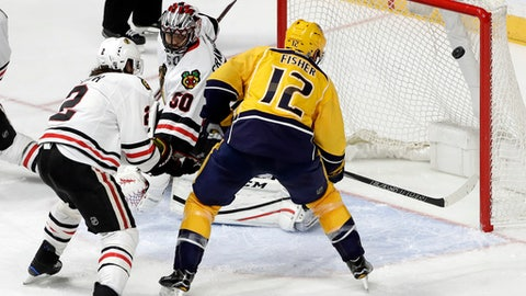 Nashville Predators center Mike Fisher (12) scores a goal against Chicago Blackhawks goalie Corey Crawford (50) during the third period of an NHL hockey game Thursday, Dec. 29, 2016, in Nashville, Tenn. Also defending for the Blackhawks is Duncan Keith (2). (AP Photo/Mark Humphrey)