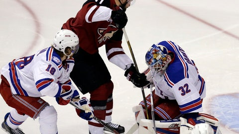 New York Rangers goalie Antti Raanta (32) makes the save on Arizona Coyotes center Martin Hanzal (11) while Marc Staal (18) defends during the third period of an NHL hockey game, Thursday, Dec. 29, 2016, in Glendale, Ariz. (AP Photo/Rick Scuteri)
