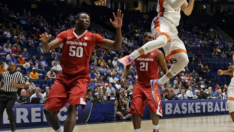 Florida's Chris Chiozza (11) passes the ball as Arkansas' Willy Kouassi (50) defends during the second half of an NCAA college basketball game in the Southeastern Conference tournament in Nashville, Tenn., Thursday, March 10, 2016. (AP Photo/Mark Humphrey)