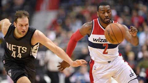 Washington Wizards guard John Wall (2) chases the loose ball next to Brooklyn Nets guard Bojan Bogdanovic (44) during the first half of an NBA basketball game, Friday, Dec. 30, 2016, in Washington. (AP Photo/Nick Wass)
