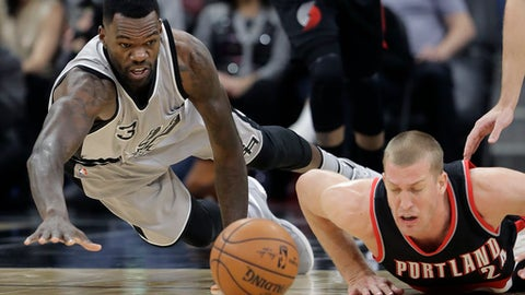 San Antonio Spurs center Dewayne Dedmon (3) dives past Portland Trail Blazers center Mason Plumlee (24) for a loose ball during the first half of an NBA basketball game, Friday, Dec. 30, 2016, in San Antonio. (AP Photo/Eric Gay)