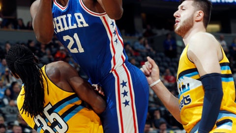 Philadelphia 76ers center Joel Embiid, center, is called for an offensive foul as he drives to the basket between Denver Nuggets forward Kenneth Faried, left, and center Jusuf Nurkic, of Bosnia, in the first half of an NBA basketball game Friday, Dec. 30, 2016, in Denver. (AP Photo/David Zalubowski)
