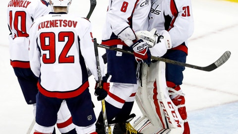 Washington Capitals left wing Alex Ovechkin (8), of Russia, and goalie Philipp Grubauer, of Germany, hug as teammates Evgeny Kuznetsov (92), of Russia, and Brett Connolly (10) approach after beating the New Jersey Devils 6-2 in an NHL hockey game, Saturday, Dec. 31, 2016, in Newark, N.J. (AP Photo/Julio Cortez)