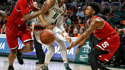 Miami guard Bruce Brown (11) works between North Carolina State guards Markell Johnson (11) and Terry Henderson (3) during an NCAA college basketball game Saturday, Dec. 31, 2016, in Coral Gables, Fla. (Al Diaz/Miami Herald via AP)