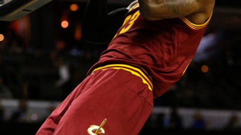 Cleveland Cavaliers forward LeBron James does a pull-up on the rim before the start of the game as Cleveland plays the Charlotte Hornets in the first half of an NBA basketball game in Charlotte, N.C., Saturday, Dec. 31, 2016. (AP Photo/Nell Redmond)