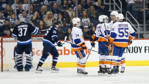 New York Islanders' Thomas Hickey (14), Shane Prince (11) and Johnny Boychuk (55) celebrate Prince's goal against Winnipeg Jets goaltender Connor Hellebuyck (37) during the second period of an NHL hockey game Saturday, Dec. 31, 2016, in Winnipeg, Manitoba. (John Woods/The Canadian Press via AP)