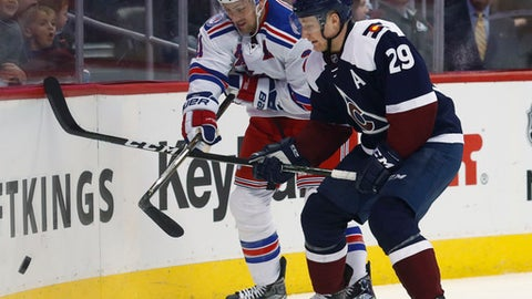 New York Rangers center Derek Stepan, left, fights for control of the puck with Colorado Avalanche center Nathan MacKinnon in the second period of an NHL hockey game Saturday, Dec. 31, 2016, in Denver. (AP Photo/David Zalubowski)