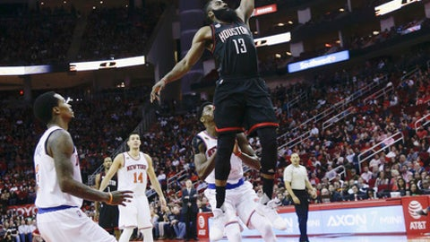 Houston Rockets guard James Harden (13) drives through the lane past New York Knicks guard Justin Holiday (8) and guard Brandon Jennings, left, during the second half of an NBA basketball game Saturday, Dec. 31, 2016, in Houston. (AP Photo/Bob Levey)