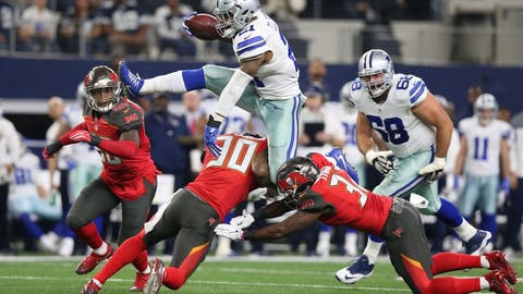 Dec 18, 2016; Arlington, TX, USA; Dallas Cowboys running back Ezekiel Elliott (21) leaps over Tampa Bay Buccaneers safety Bradley McDougald (30) and safety Keith Tandy (37) in the first quarter at AT&T Stadium. Mandatory Credit: Matthew Emmons-USA TODAY Sports