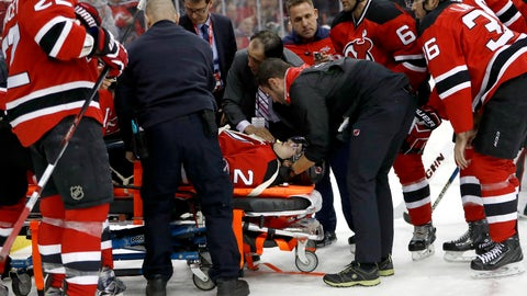 Trainers load New Jersey Devils defenseman John Moore onto a stretcher to pull him off the ice after he was injured during the first period of an NHL hockey game against the Washington Capitals, Saturday, Dec. 31, 2016, in Newark, N.J. (AP Photo/Julio Cortez)