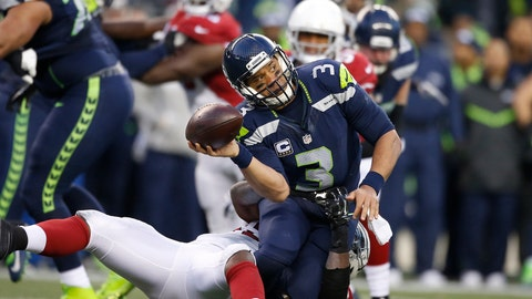 SEATTLE, WA - DECEMBER 24:  Quarterback Russell Wilson #3 of the Seattle Seahawks passes as he's tackled by the Arizona Cardinals at CenturyLink Field on December 24, 2016 in Seattle, Washington.  (Photo by Otto Greule Jr/Getty Images)
