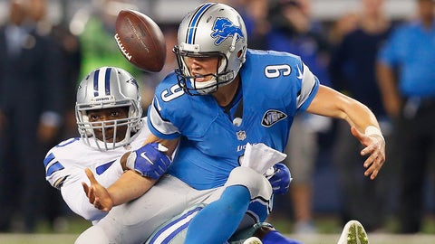 ARLINGTON, TX - JANUARY 04:  Quarterback Matthew Stafford #9 of the Detroit Lions fumbles the ball after being sacked by defensive end Demarcus Lawrence #90 of the Dallas Cowboys in the fourth quarter during a NFC Wild Card Playoff game at AT&T Stadium on January 4, 2015 in Arlington, Texas.  (Photo by Tom Pennington/Getty Images)