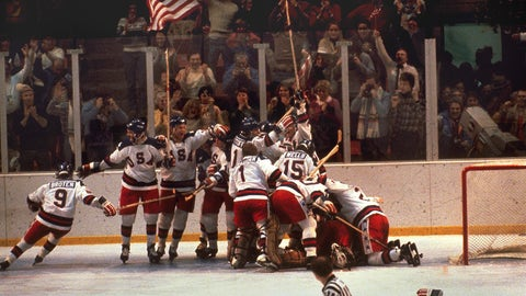 The U.S. hockey team pounces on goalie Jim Craig after a 4-3 victory against the Soviets in the 1980 Olympics, as a flag waves from the partisan Lake Placid, N.Y. crowd, February 22, 1980.  (AP Photo)