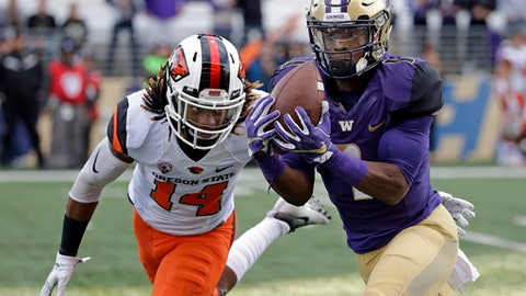 FILE - In this Oct. 22, 2016, file photo,Washington's John Ross, right, makes a long pass reception in front of Oregon State's Treston Decoud in the first half of an NCAA college football game in Seattle. Ross is the player of the year on the Associated Press All-Pac-12 team announced on Friday, Dec. 9, 2016.  (AP Photo/Elaine Thompson, File)