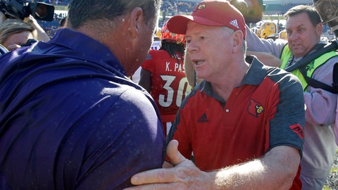 LSU head coach Ed Orgeron, left, and Louisville head coach Bobby Petrino greet each other at the end of the Citrus Bowl NCAA college football game, Saturday, Dec. 31, 2016, in Orlando, Fla. LSU won 29-9. (AP Photo/John Raoux)
