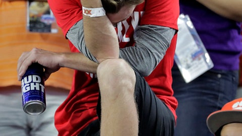An Ohio State fan reacts during the second half of the team's Fiesta Bowl NCAA college football playoff semifinal against Clemson, Saturday, Dec. 31, 2016, in Glendale, Ariz. Clemson won 31-0 to advance to the BCS championship game against Alabama. (AP Photo/Rick Scuteri)