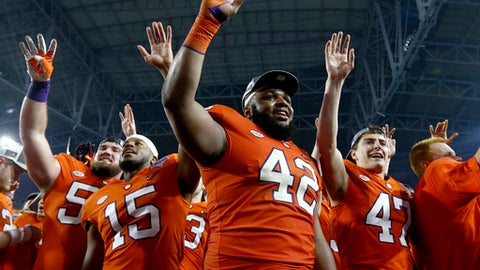 Clemson defensive lineman Christian Wilkins (42), safety Korrin Wiggins (15) and kicker Alex Spence (47) smile and wave after Clemson defeated Ohio State 31-0 in the Fiesta Bowl NCAA college football playoff semifinal, Saturday, Dec. 31, 2016, in Glendale, Ariz. Clemson advanced to the BCS championship game Jan. 9 against Alabama. (AP Photo/Ross D. Franklin)