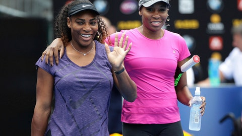 United States' Serena Williams, left, waves to the crowd as she walks onto the court with her sister Venus during an exhibition event ahead of the ASB Classic tennis tournament in Auckland, New Zealand, Sunday, Jan. 1, 2017. (Doug Sherring/New Zealand Herald via AP)