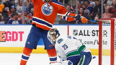 Edmonton Oilers' Patrick Maroon (19) celebrates a teammate's goal against Vancouver Canucks goalie Jacob Markstrom (25) during the second period of an NHL hockey game Saturday, Dec. 31, 2016, in Edmonton, Alberta. (Jason Franson/The Canadian Press via AP)