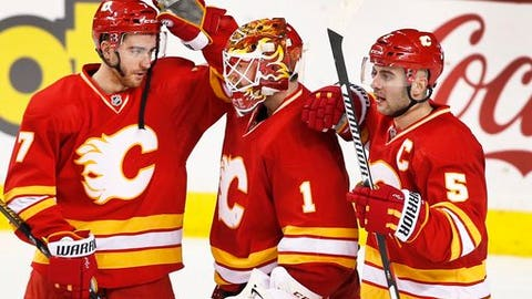 Calgary Flames goalie Brian Elliott, center, is congratulated by TJ Brodie, left, and Mark Giordano celebrate the team's 4-2 victory over the Arizona Coyotes in an NHL hockey game Saturday, Dec. 31, 2016, in Calgary, Alberta. (Larry MacDougal/The Canadian Press via AP)