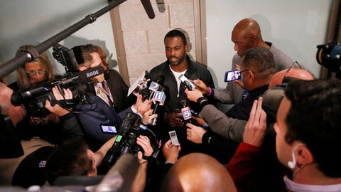 Former NFL quarterback Michael Vick speaks with reporters before the first half of an NFL football game between the Atlanta Falcons and the New Orleans Saints, Sunday, Jan. 1, 2017, in Atlanta. The Falcons say Vick is among numerous former players and coaches who will take part in a halftime ceremony during a game against the New Orleans Saints. (AP Photo/John Bazemore)