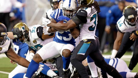 Indianapolis Colts running back Frank Gore (23) is tackled by Jacksonville Jaguars safety Johnathan Cyprien (37) during the first half of an NFL football game in Indianapolis, Sunday, Jan. 1, 2017. (AP Photo/Michael Conroy)