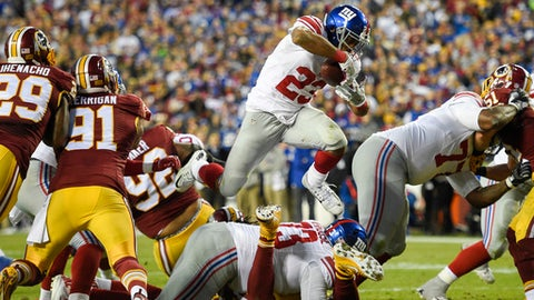 New York Giants running back Rashad Jennings (23) leaps over offensive guard Marshall Newhouse (73) and through the Washington Redskins defensive line during the first half of an NFL football game in Landover, Md., Sunday, Jan. 1, 2017. (AP Photo/Nick Wass)