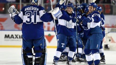 Toronto Maple Leafs goalie Frederik Andersen (31) celebrates with teammates Roman Polak (46) and Tyler Bozak (42) following overtime NHL Centennial Classic hockey action against the Detroit Red Wings, in Toronto, Sunday, Jan. 1, 2017. (Frank Gunn/The Canadian Press via AP)